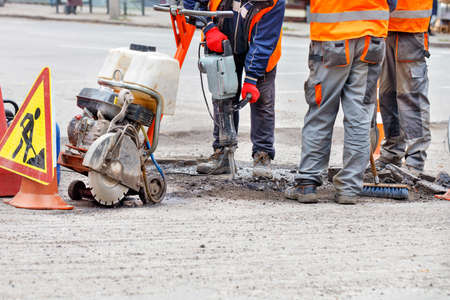 Three road service personnel in reflective clothing on a fenced-in section of road repair the roadway using a hand-held road tool and a jackhammer. 免版税图像