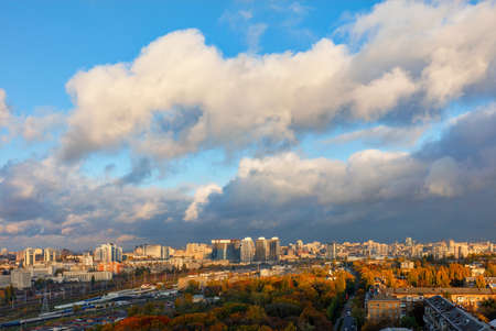 The sun's rays break through gray clouds, exposing the blue of the sky and brightly illuminating the autumn cityscape of Kyiv. Bird's-eye view. 免版税图像