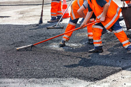 A working group of road workers in orange overalls renews a section of the road with fresh hot asphalt and smooths it out for repair with metal levels. 免版税图像