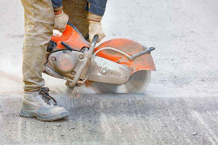 A worker repairs a section of road, cuts worn asphalt in a cloud of dust with a portable asphalt cutter and a diamond cutting disc, copy space, close-up.