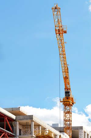 A tower crane jib leaps up over a construction site against a clear blue sky, vertical image, copy space. 免版税图像