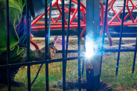 Bright sparks from electric welding scatter in different directions against the background of a working welder and a metal fence in blur.