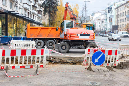 Emergency road vehicles, an excavator and a truck are working on the repair of the heating main, the dug trench on the sidewalk of the city street is fenced off.