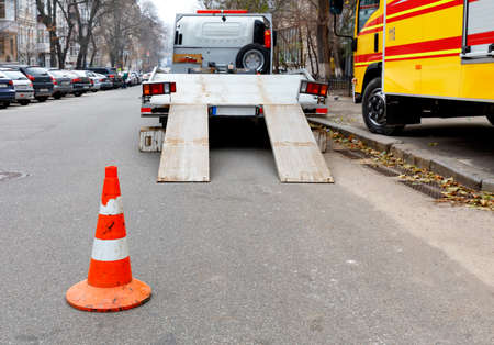 A bright orange traffic cone stands on the dark asphalt and fences the roadway with a parked transport truck.