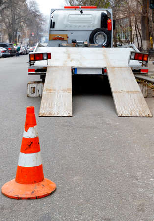 A bright orange traffic cone stands on the dark asphalt and fences the roadway with a parked transport truck, vertical image, copy space.