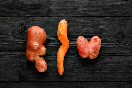 Beautifully deformed vegetables, ugly funny potatoes in the shape of a heart and letters and twisted carrots on a black wooden background. Waste prevention concept top view. Top view, copy space.