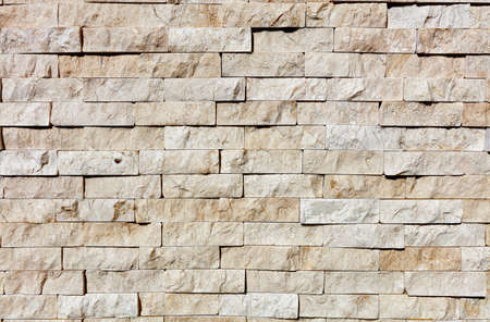 Wall background and texture of chopped yellow sandstone, close up.