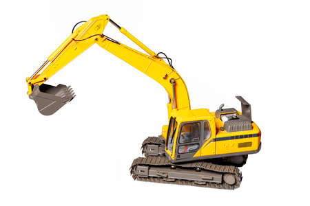 Toy model of a yellow construction excavator isolated on a white background, selective focus.