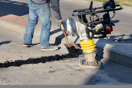 Cold asphalt is used by road workers to repair and seal cracks on the roadway on a bright sunny day, against the backdrop of a rammer. 免版税图像