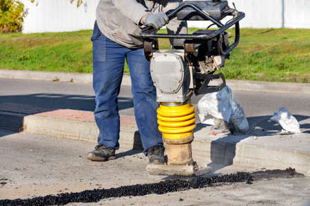 A road worker uses a petrol vibratory rammer to repair asphalt on the roadway on a bright sunny day. 免版税图像