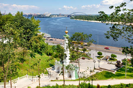 Beautiful summer cityscape of Kyiv with a view of the mountainside, the Dnipro river with many bridges and a Column to the Magdeburg Law.
