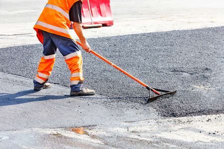 While repairing the road, the road builder levels the fresh asphalt with a metal level against the background of smooth fresh asphalt. Copy space, selective focus.