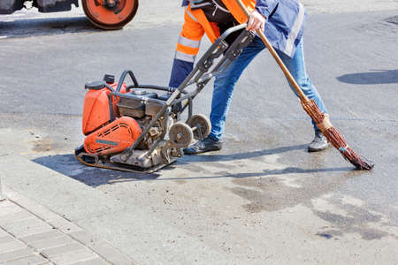 A road worker adjusts the operation of a petrol vibratory compactor against the background of a vibratory roller, and holds an old broom for asphalting a small section of the road. Copy space.