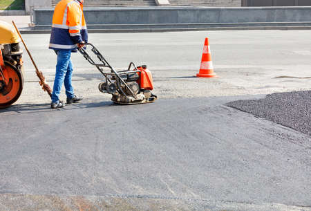 A road worker compacts asphalt on a fenced road section of the roadway with a petrol vibration compactor.