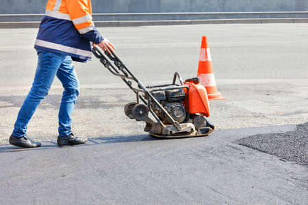 A road worker compacts asphalt on the carriageway with a petrol vibratory plate compactor.