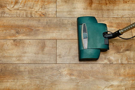 Remove dust from wood textured floor with a vacuum cleaner, copy space.