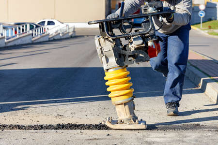 A road worker operates a vibratory rammer to asphalt a small area on a bright sunny day. Copy space, selective focus.