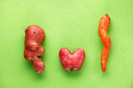 Ugly funny vegetables, lumpy potatoes in the shape of a heart and letters and a twisted carrot on a green plaster background. Coarse vegetables or food waste concept. Top view, copy space.