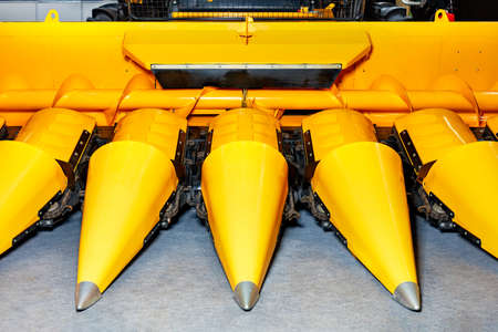 Front of sharp cones of yellow corn harvester, close-up.