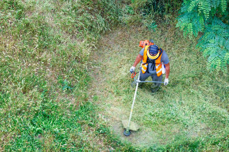 A utility worker in reflective clothing mows tall green grass with a petrol trimmer in circular motions. Copy space, top view.