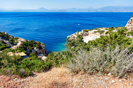 Hard shrub grows on the rocky slopes of the Greek Gulf of Corinth against the backdrop of a lagoon on the coast in blur, beautiful top view. Copy space.