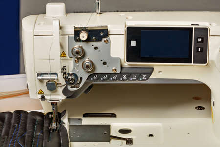 Modern professional sewing machine for sewing upholstery of furniture from various dense fabrics, the working part of the sewing machine close-up. Copy space.