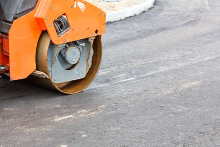 The metal cylinder of a large vibratory roller powerfully compacts the fresh asphalt of the road surface. Close-up, copy space.