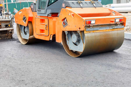 The metal cylinders of the large vibratory roller roll on the new road surface after the hot asphalt operator has poured the asphalt, providing a powerful compaction of the new road.