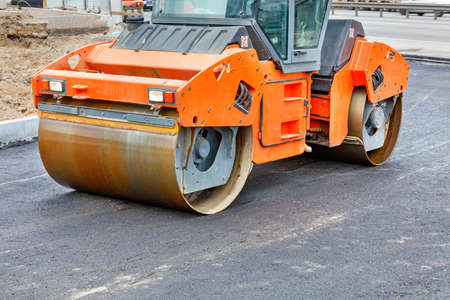 The metal cylinders of the large vibratory roller roll over the new road surface for powerful compaction of the fresh asphalt.