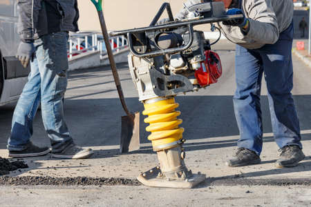 Road workers use vibratory rammer to asphalt a small section of road on a bright sunny day, selective focus. 免版税图像