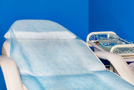 Physiotherapy room with massage couch covered with disposable non-woven cape and bedside table in the doctor's office. Blue background, copy space.