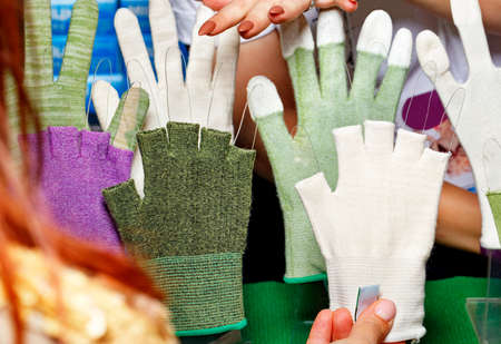 Women's bright gloves, fingerless and full-fingered from fabric of various colors, women's hands make a choice. 免版税图像
