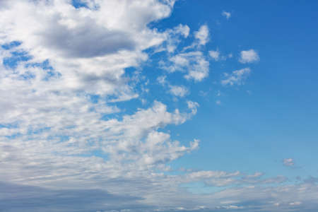 White fluffy clouds spread across the sky, revealing pure blue and splitting the picture in half.