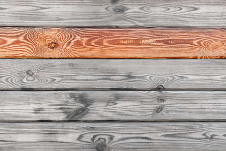 Old gray wood wall with yellow fresh plank highlighted at the top, background and texture photo texture, copy space.