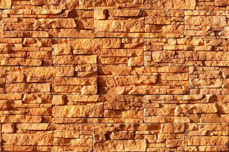 Sunlight hard illuminates an orange stone background from old tiles.