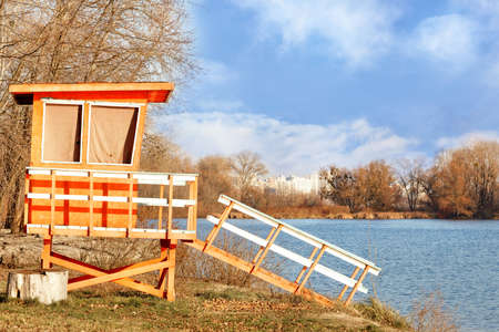 A lonely wooden lifeguard house on the river bank is illuminated by the rays of the bright sun against the background of a blue sky and urban development on the horizon.