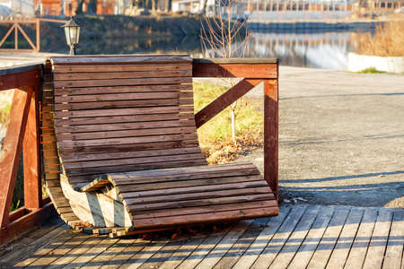 A wooden armchair with horizontal slats sits in a seating area by the river and is illuminated by the rays of the bright autumn sun.
