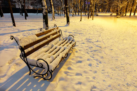 Empty brown wooden bench with metal decorative railing in the snow under the warm light of a street lamp on a winter evening in a city park. 免版税图像