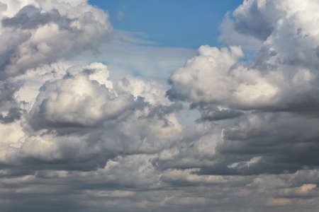 Cumulus white-gray clouds gradually cover the blue sky with a dense blanket.