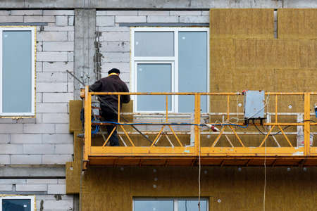 The builder insulates the facade of the house with mineral wool using a construction cradle. 免版税图像