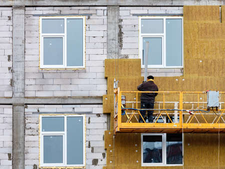 The builder insulates the facade of a house under construction with mineral insulation around the windows using a construction cradle and an aluminum profile, the concept of heat saving in the house.