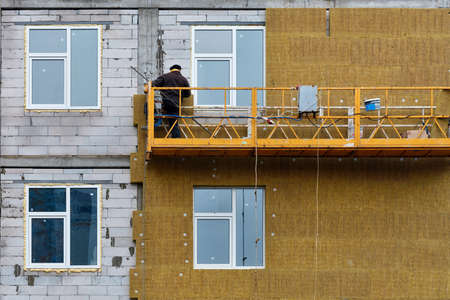 The builder insulates the facade of the house under construction with mineral insulation around the windows using a suspended platform, which is a concept of saving heat in the house, copy space. 免版税图像