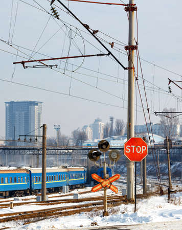 Red stop sign at a railway crossing against the background of railway tracks, blue train carriages and cityscape at the entrance to the city, winter cityscape, vertical image.