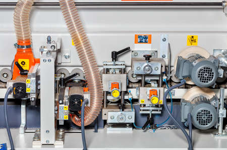 The device of a modern automatic woodworking machine with a system of motors, rollers and an air intake for removing sawdust and shavings. Reklamní fotografie