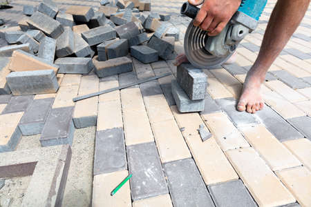A worker with a grinder with a diamond cutting wheel trims paving slabs, standing barefoot and holding a stone cobblestone with one foot. Copy space.