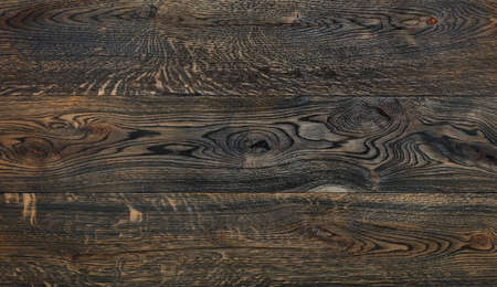Old wooden background from dark brown horizontal planks texture with grains, cracks and knots.