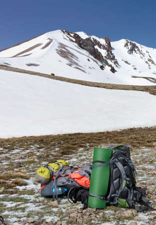 Camping gear, rucksacks, paddles, and a folded camping tent are positioned against a snow-capped mountain of Erciyes and clear blue skies in blur. Vertical image, copy space.