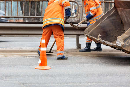 Road service workers in bright orange reflective uniforms use shovels to remove accumulated sand and debris between lanes by loading it into a metal grader bucket. Reklamní fotografie