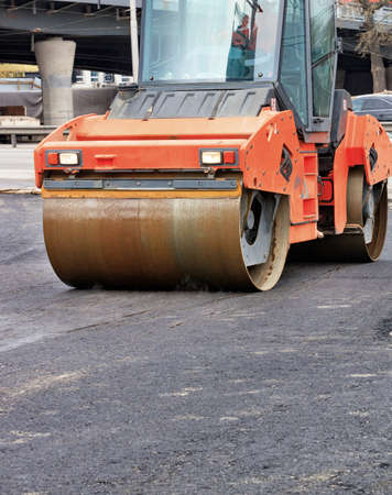 A heavy vibratory roller compresses hot asphalt on a working stretch of roadway on a clear, sunny day. Vertical image, copy space.