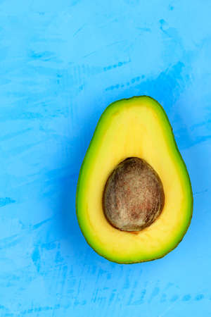 Half a ripe avocado with yellow flesh and pith on a light turquoise surface. The concept of a healthy, wholesome food. Vertical image, copy space, close-up.